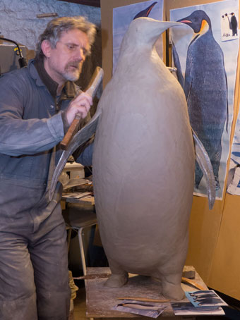 Sculptor Nick Bibby working on his Emperor Penguin